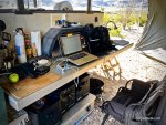 outdoor office setup under expansive awning of off-road camping trailer in desert environment