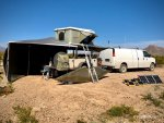 Van and offroad trailer with rooftop tent and awning deployed, camping in off-grid  desert environment.