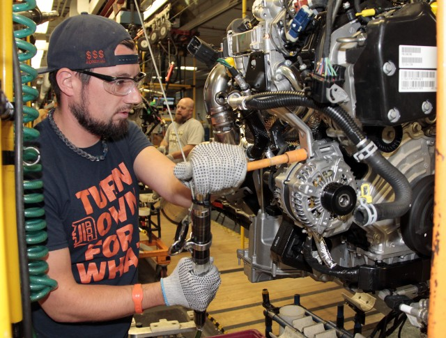 Jared Omell makes final touches to an EcoDiesel engine prior to installation at Warren Truck Assembly Plant