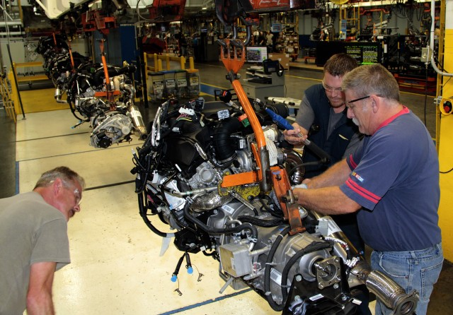 Mark Blake, Charles Vanatta and David Coutts inspect an EcoDiesel engine and 8-speed transmission prior to installation at Warren Truck Assembly Plant
