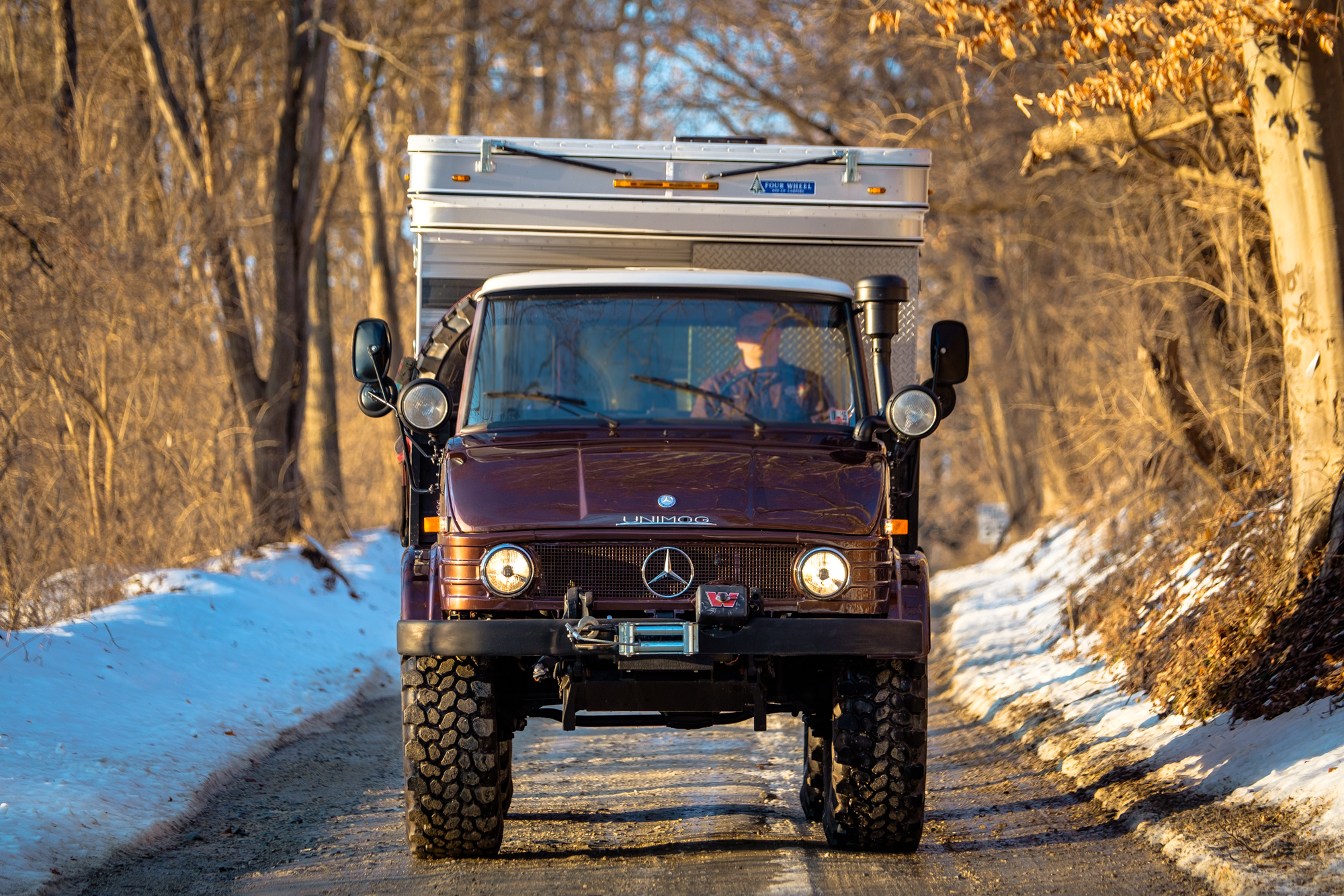 Front view of the Unimog Off Road Mercedes cruising down a snowy road