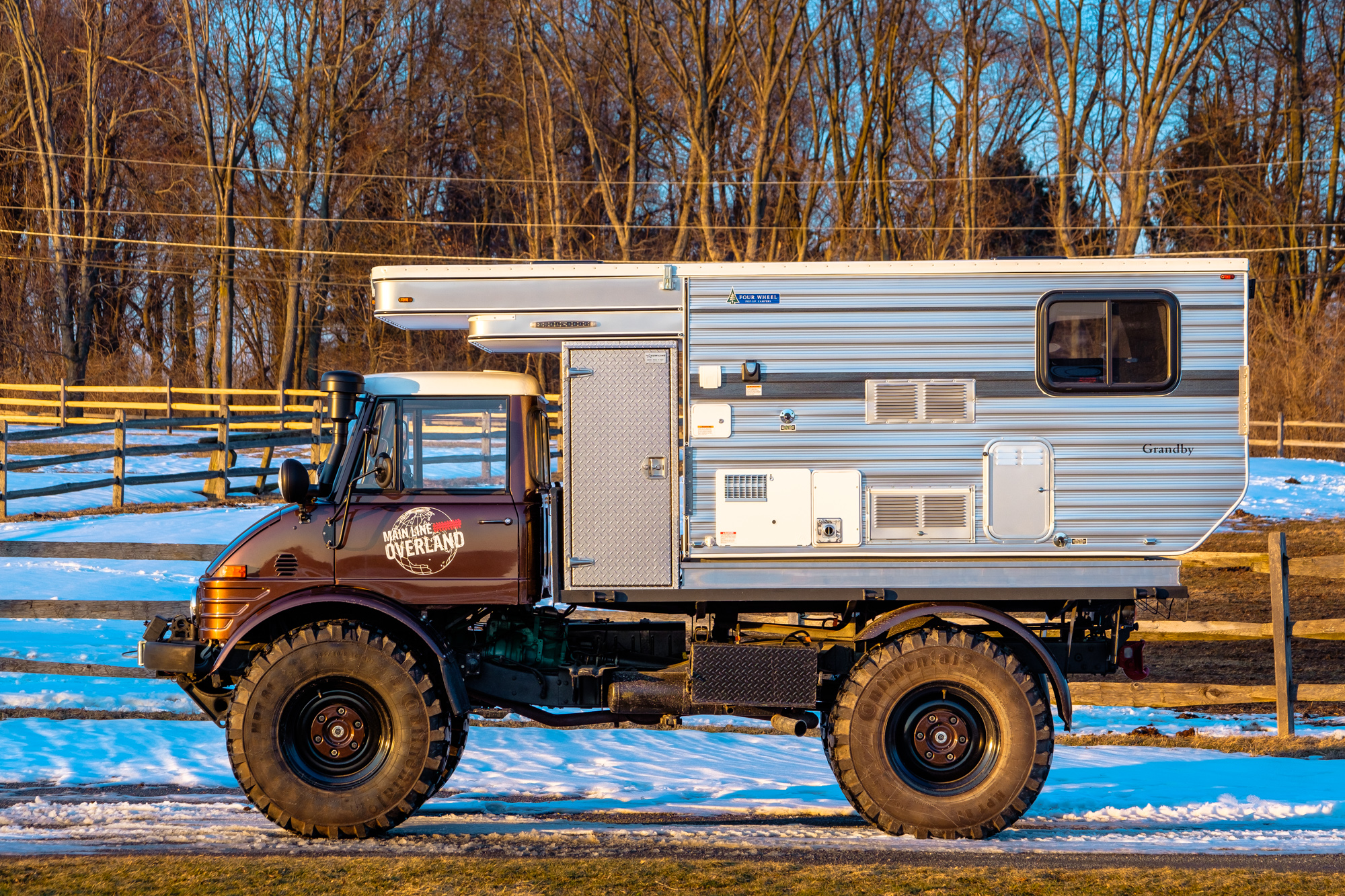 A side view of the Unimog Off Road Mercedes with a Four Wheel Campers Grandby camping pod mounted to the back.